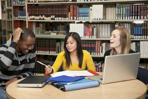College students studying in a library of books